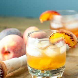 Roasted Peach Old Fashioned cocktail combines caramelized roasted peaches, orange bitters, and bourbon whiskey to make a classic drink even better. http://www.mamagourmand.com