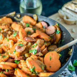 Sweet potato goulash with smoked sausage and caramelized onions recipe - so easy and delicious to throw together for a weeknight dinner. Serve with crusty bread and a fresh salad and it's a healthy and gluten free dinner recipe! www.mamagourmand.com