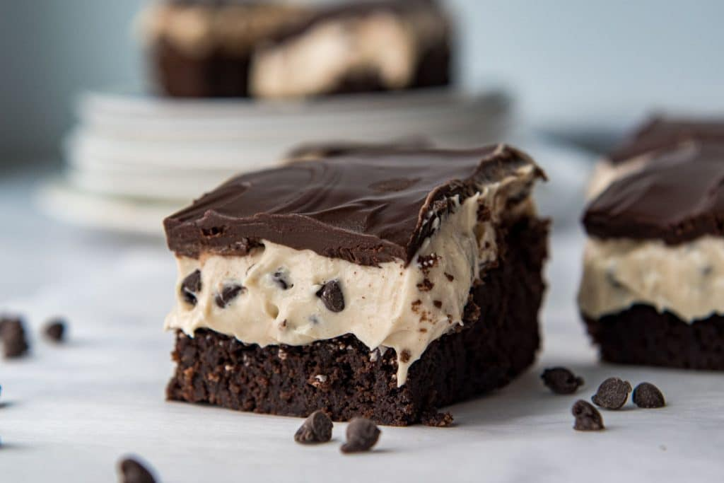 a cut cookie dough brownie with chocolate chips laying around it