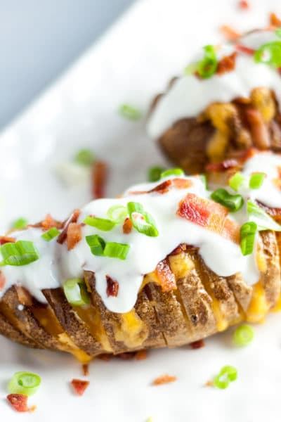 Loaded cheesy potatoes hasselback recipe- easy but elegant dinner companion that can be made for an easy weeknight dinner or to impress dinner guests. www.mamagourmand.com