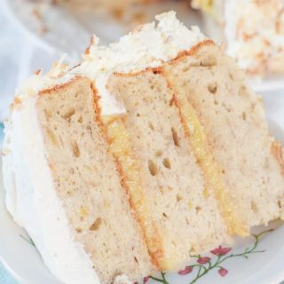 This Banana Cake with Fresh Banana Curd Cake recipe is has fluffy banana cake layers with a homemade fresh banana curd filling and whipped cream frosting. Welcome to cake heaven! https://www.mamagourmand.com