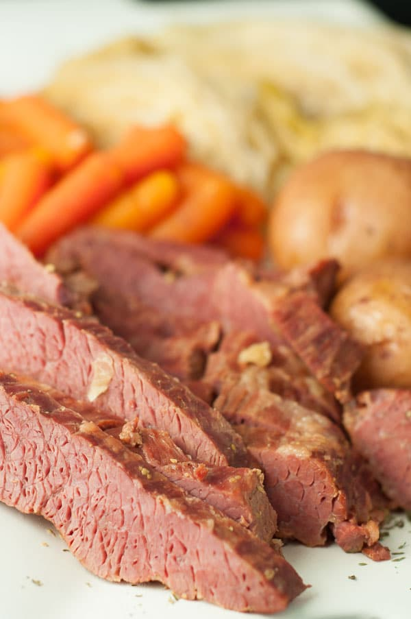 Cut pieces of corned beef on a plate from the Slow Cooker Apple and Brown Sugar Corned Beef and Cabbage recipe