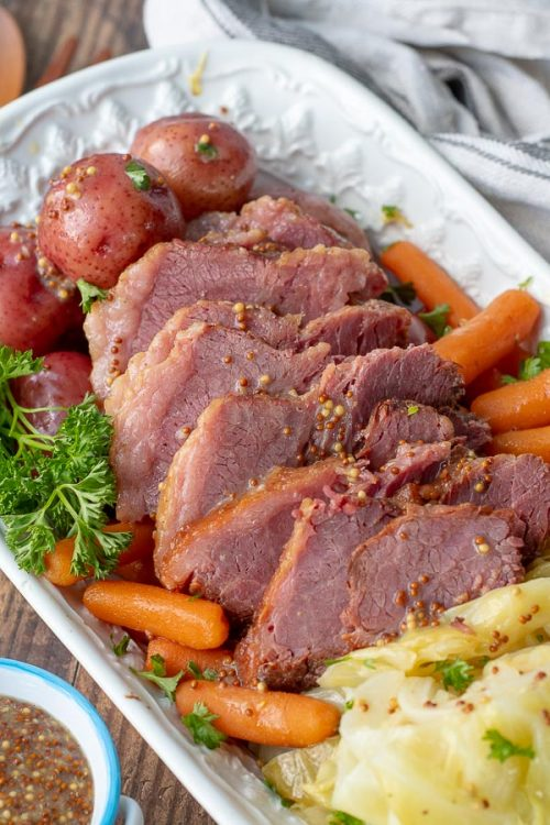 an overhead shot of a platter of slow cooker corned beef and cabbage with potatoes and carrots