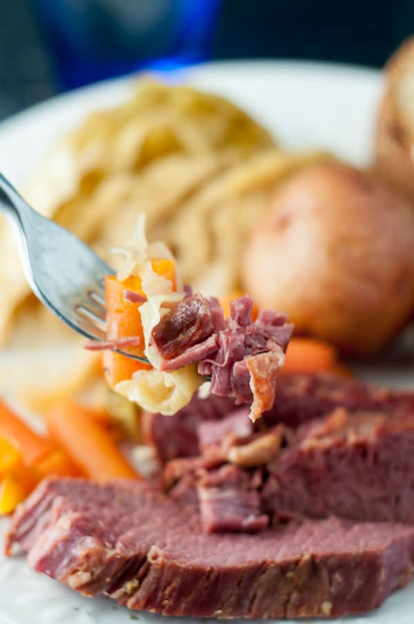 A close up picture of a bite of Slow Cooker Apple and Brown Sugar Corned Beef and Cabbage