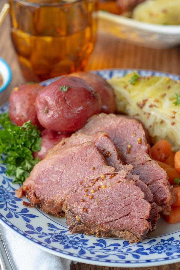 a close up of a plate of sliced corned beef, cabbage, potatoes, and carrots