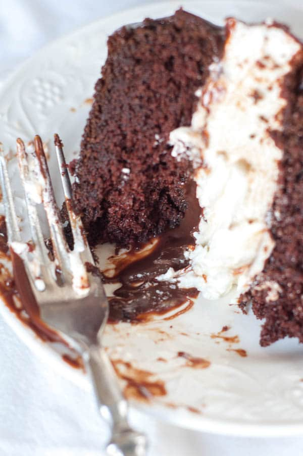 A half eaten slice of Salted Chocolate Ganache Ding Dong Cake on a plate with a fork resting by it.