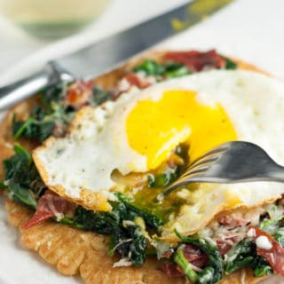Spinach, Crispy Proscuitto, Egg Socca Pizza is a gluten free and healthy way to get your pizza fix. This quick, easy, and healthy recipe is perfect for a weeknight dinner. https://www.mamagourmand.com