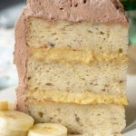 a piece of fluffy banana cake with banana filling standing straight up on a plate