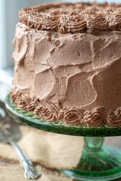 a banana cake on a green cake stand with chocolate whipped cream frosting all over it