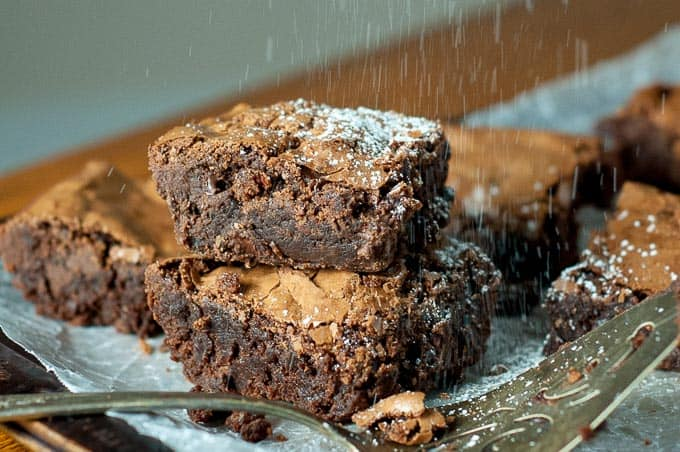 two fudgy brownies stacked on top of each on a baking sheet with powdered sugar sprinkled over top