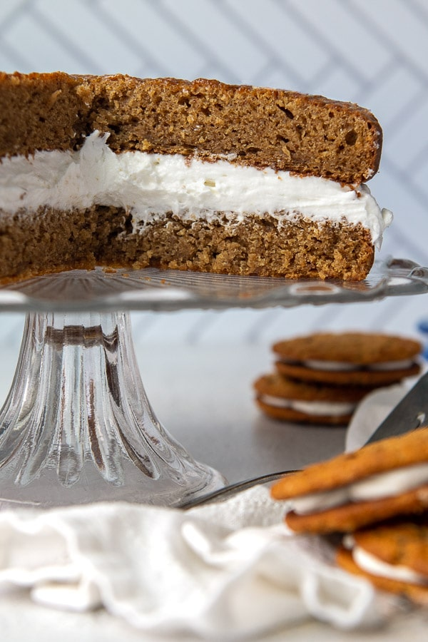 a giant oatmeal creme pie on a cake stand with little debbie snack cakes around it