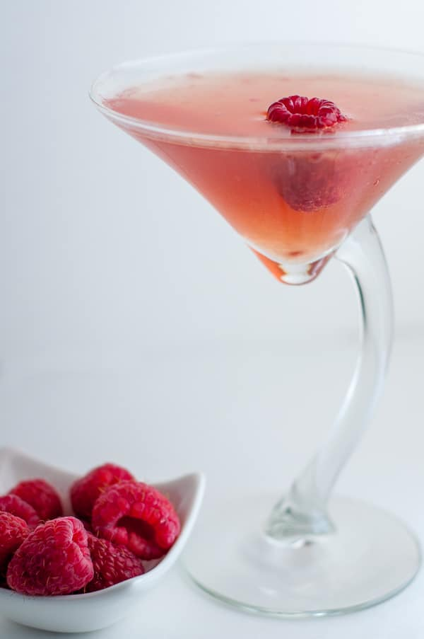 straight on shot of raspberry martini drink with fresh raspberries next to it