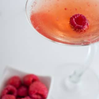 close up of raspberry martini cocktail with a bowl of fresh raspberries next to it