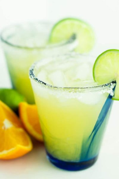 two glasses of skinny margarita with sliced oranges and limes lying next to them