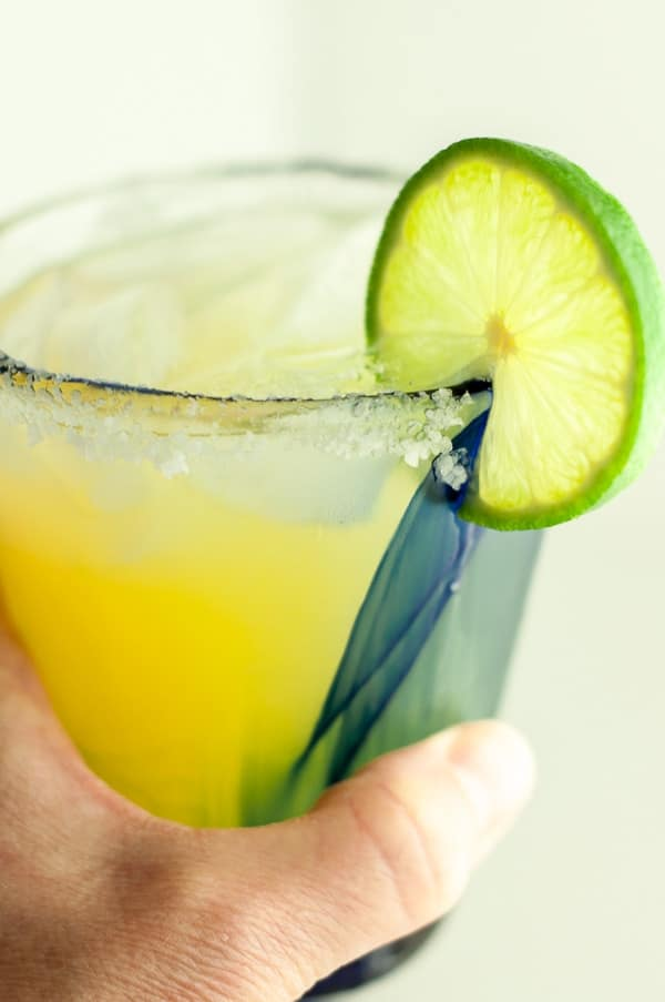 a hand holding up a glass of skinny margarita