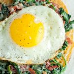 overhead shot of spinach, egg, prosciutto socca pizza on a white plate