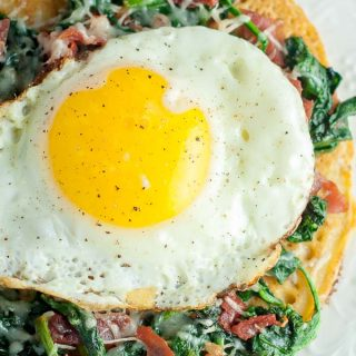 overhead shot of spinach, egg, prosciutto socca pizza on a white plate