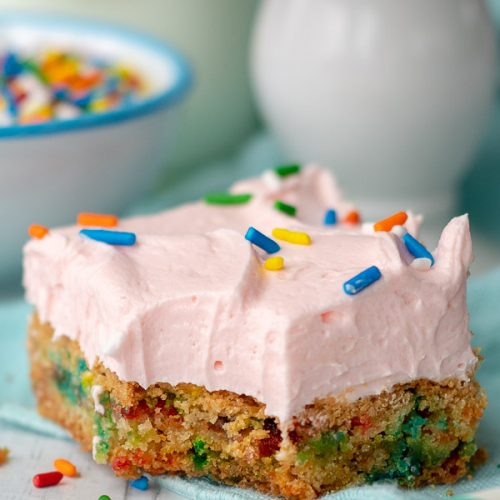 a close up of a sugar cookie bar with a bite taken out resting on a table