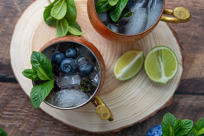 overhead shot of two fruity moscow mules on a wooden circle board with blueberries and fresh mint