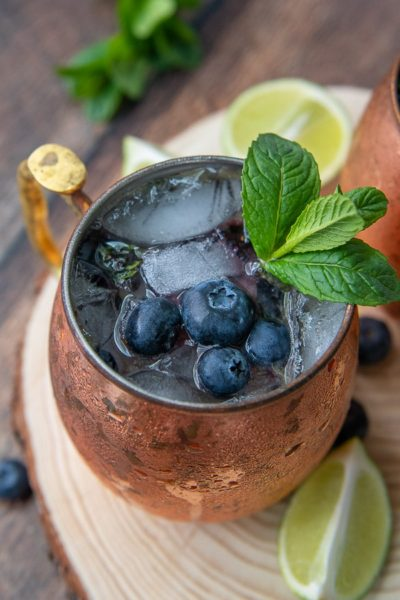 a side angle shot of blueberry moscow mule with fresh lime wedges laying next to it