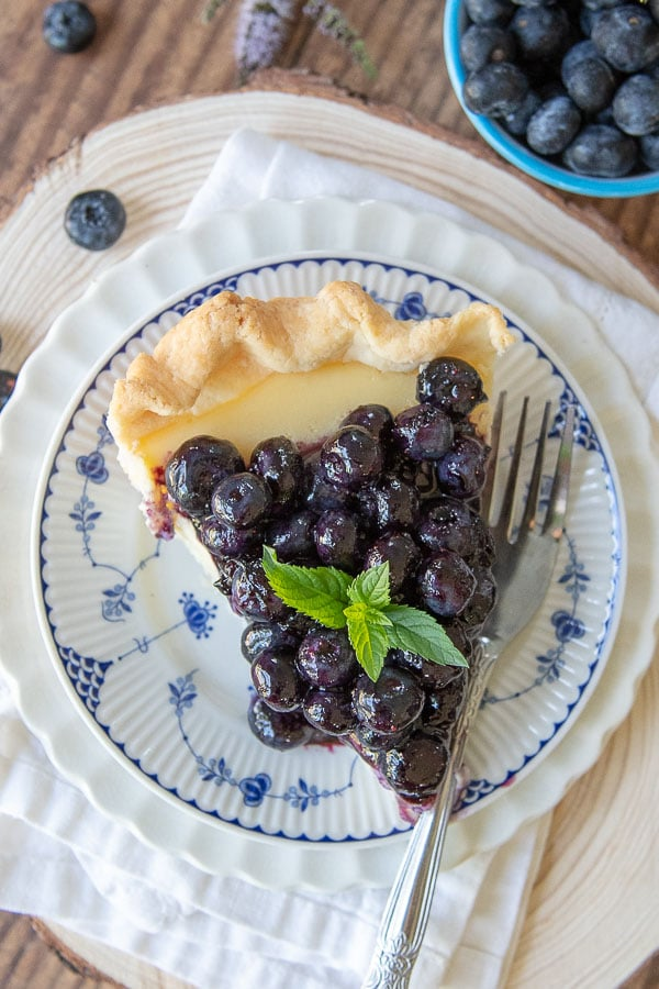 overhead shot of a slice of fresh blueberry pie on a white plate with small blue flowers and a napkin underneath