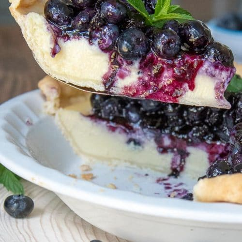 a pie server lifting a slice of blueberry cream pie out of a pie dish