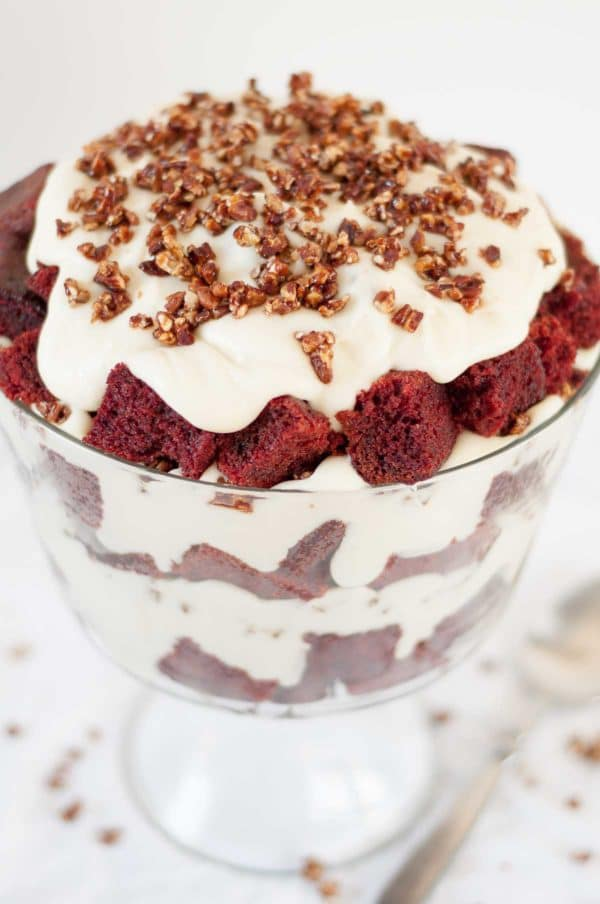 Red velvet trifle with mascarpone whipped topping combines a moist red velvet cake, a mascarpone whipped cream topping, and candied pecans. It will impress a crowd, but it's so easy to throw together! https://www.mamagourmand.com