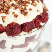 Delicious, moist red velvet cake trifle layered with a mascarpone whipped cream topping, and candied pecans will impress a crowd, but it's so easy to throw together! https://www.mamagourmand.com