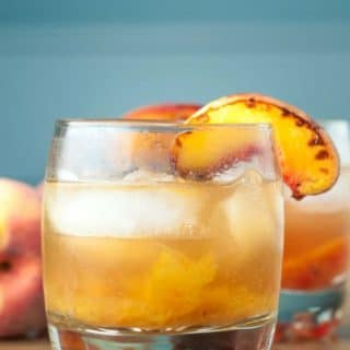Roasted Peach Old Fashioned cocktail combines caramelized roasted peaches, orange bitters, and bourbon whiskey to make a classic drink even better. https://www.mamagourmand.com
