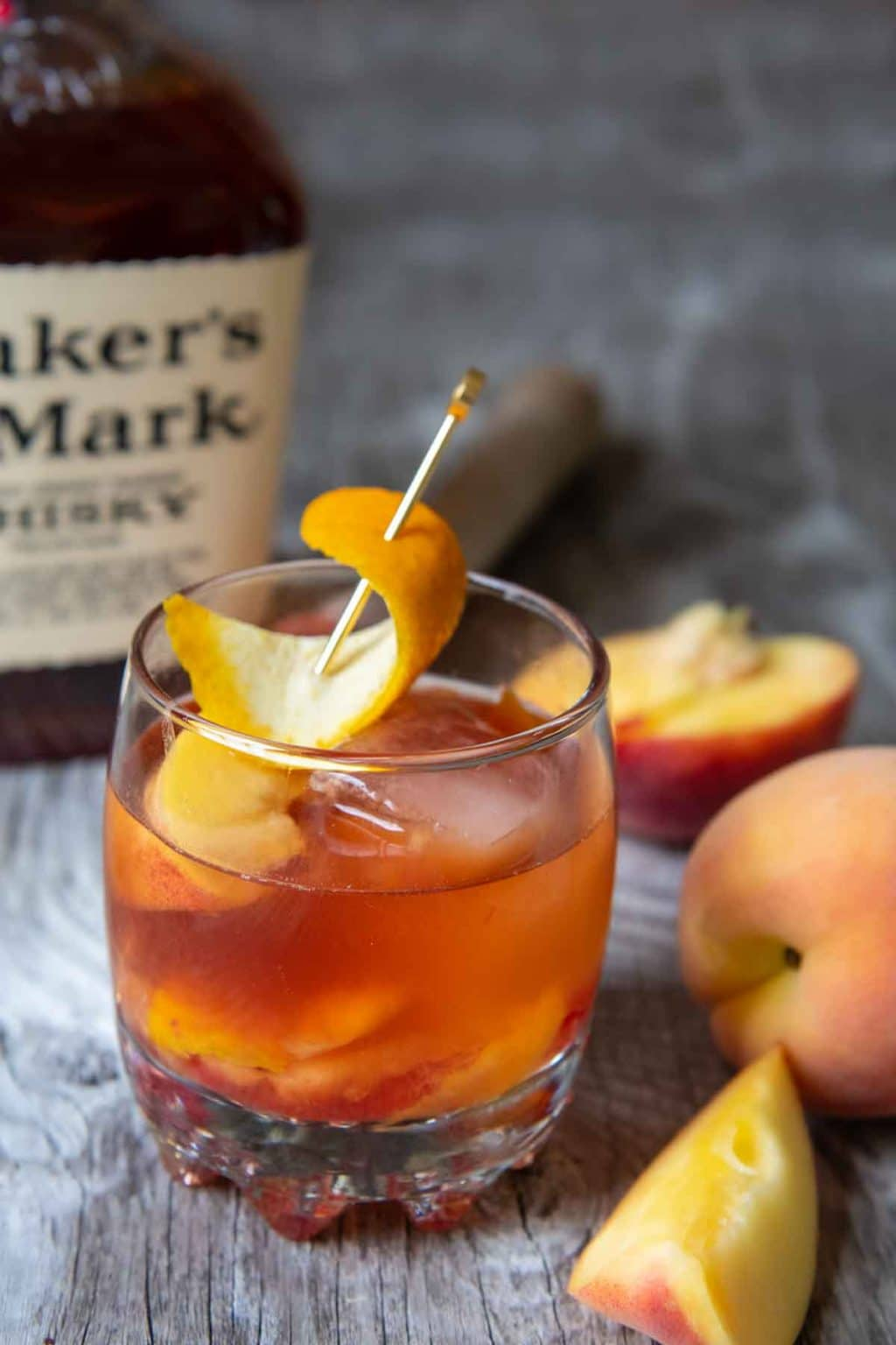 a peach old fashioned on a wood board with bourbon in the background