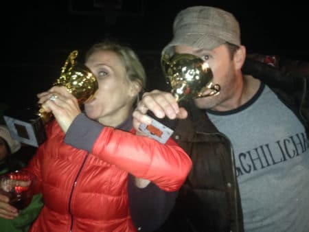 two people drinking out of trophies