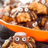 an easy spider cookie in the foreground with a plate filled in the back