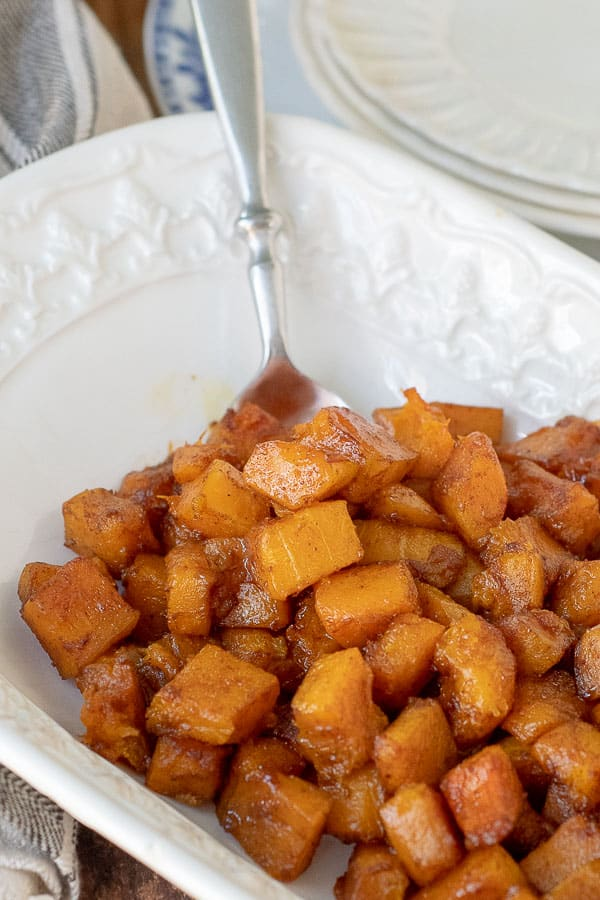 a spoon resting in a serving bowl with roasted butternut squash