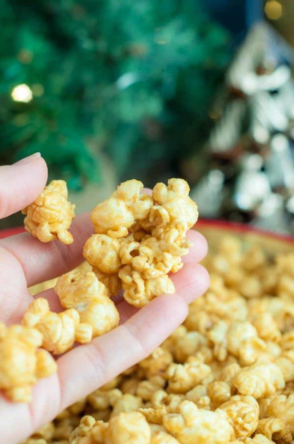 Hand holding up Mom's Easy Microwave Caramel Corn, the best caramel corn recipe ever! https://www.mamagourmand.com