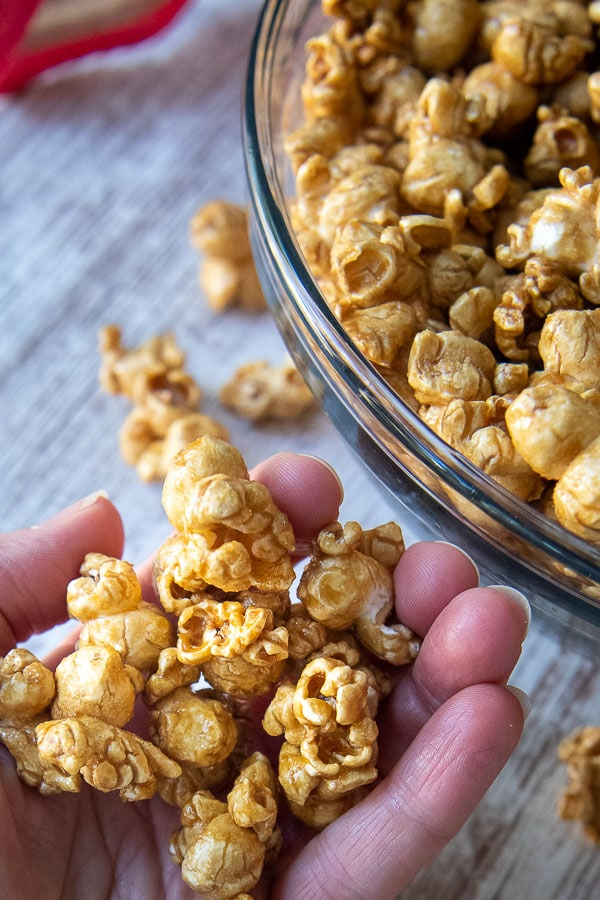 a hand holding up a scoop of homemade caramel corn recipe