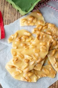 homemade peanut brittle on a piece of parchment with wrapping supplies nearby