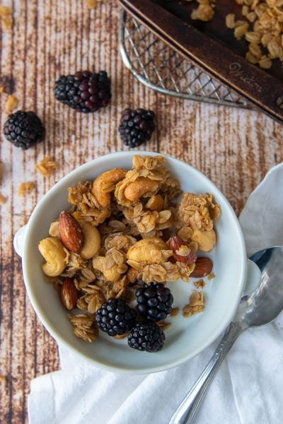 a bowl of homemade granola with milk and berries