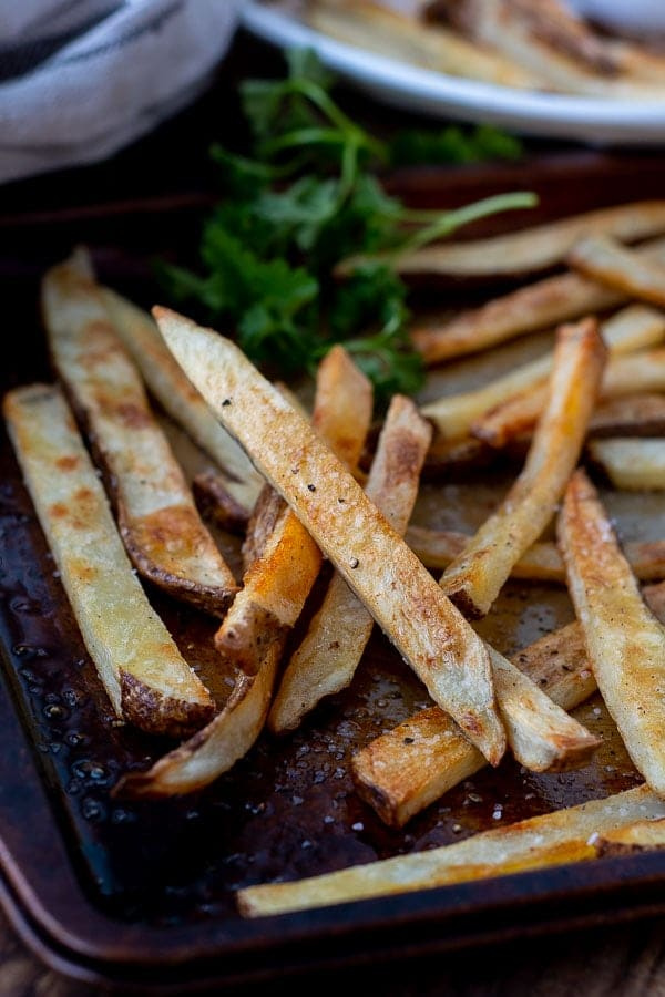 a close up of crispy oven baked fries on a baking sheet