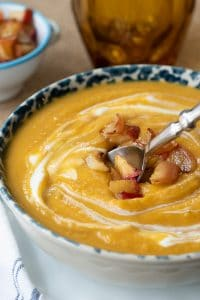 a spoon going into a bowl of roasted butternut squash soup