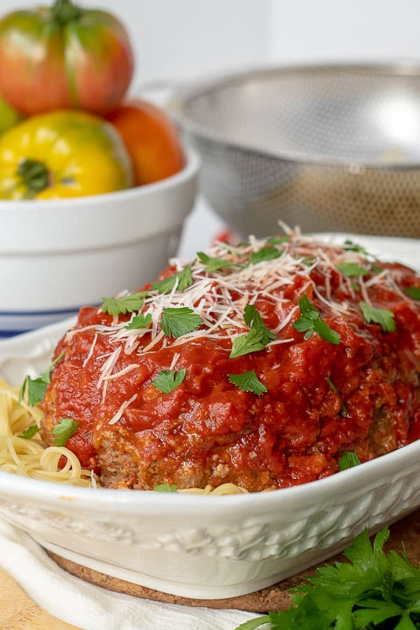 a large white serving dish with Italian meatloaf served on a bed of spaghetti