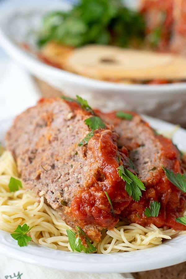 two slices of Italian meatloaf served on a spaghetti