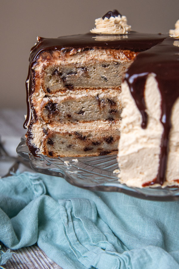 a peanut butter banana cake on a cake stand sliced to see the inside of cake