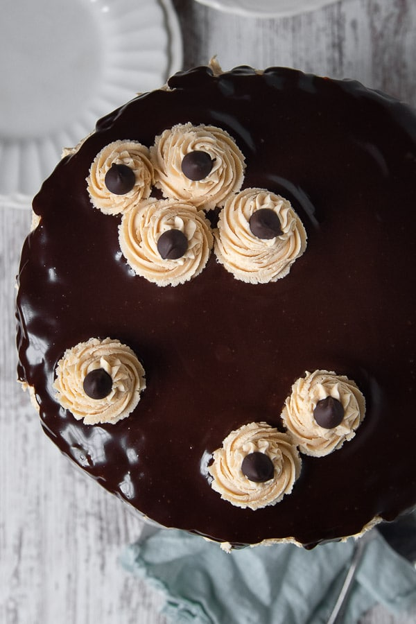 overhead shot of peanut butter banana cake with ganache and buttercream rosettes on top