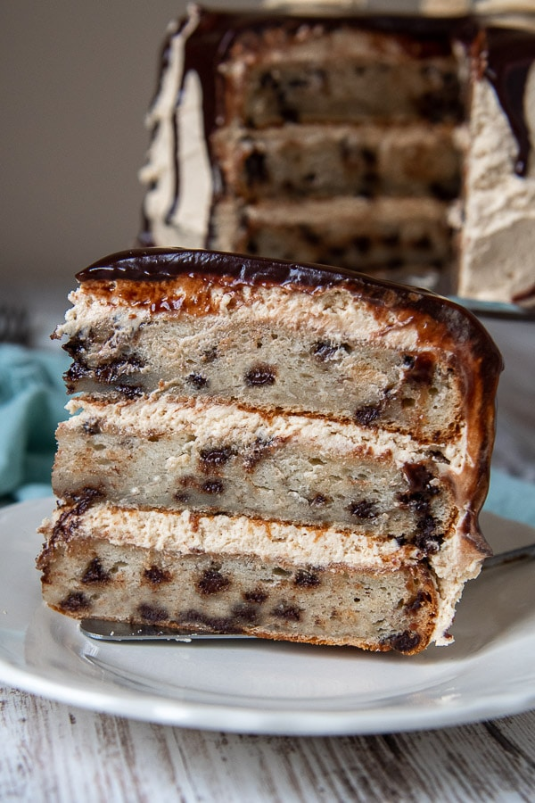 a slice of banana chocolate chip cake standing up on a white plate