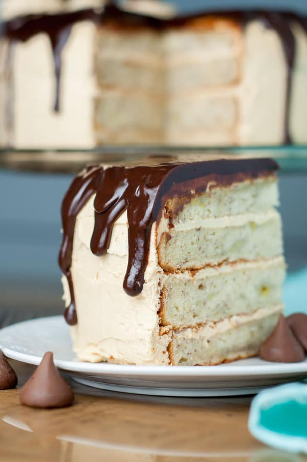 Peanut Butter Chunky Monkey Cake has fluffy peanut butter buttercream frosting, moist banana cake layers, and Nutella ganache. Best cake EVER! https://www.mamagourmand.com