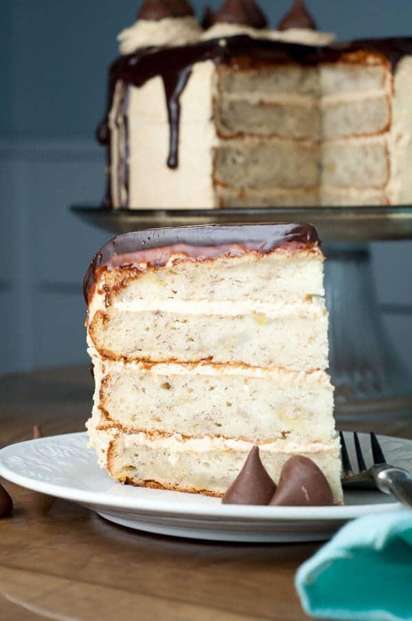 Peanut Butter Chunky Monkey Cake has fluffy peanut butter buttercream frosting, moist banana cake layers, and Nutella ganache. Best cake EVER! https://www.mamagourmand.com