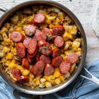overhead shot of smoked sausage slices in a skillet over potato hash with cheese