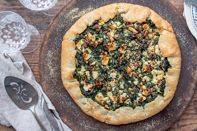 an overhead shot of vegetable tart on a baking stone with spatula resting next to it