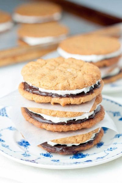 Flourless Peanut Butter Chocolate Marshmallow Sandwich cookies have a gluten free chewy peanut butter cookie with chocolate ganache and marshmallow buttercream. https://www.mamagourmand.com