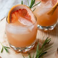two glasses of grapefruit vodka cocktails with fresh rosemary laying next to it
